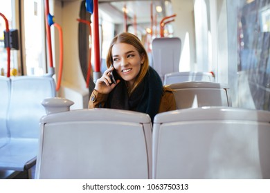 Young happy woman sitting in city bus and talking on mobile phone.