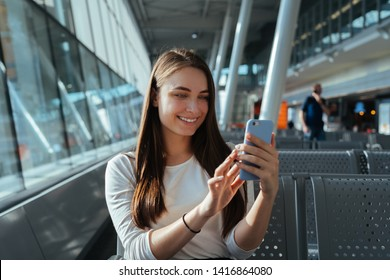 Young happy woman sitting at the gate and using smartphone while waiting for a flight at the airport. Travel concept. Travel passenger girl chatting and smiling at terminal departure lounge.