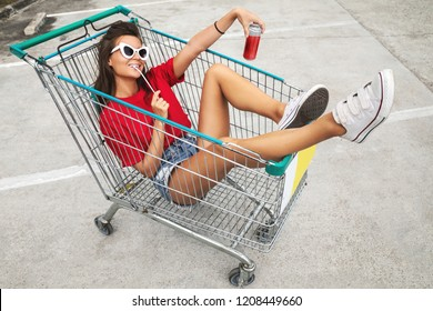 Young happy woman sitting inside a shopping cart with soft drink on the parking of supermarket
