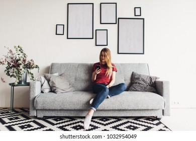 Young happy woman sitting on sofa and using mobile phone at home