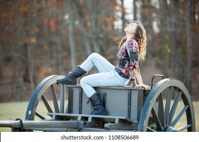 Young happy woman sitting on old cannon carriage in Manassas National Battlefield Park in Virginia where Bull Run battle was fought, sunlight