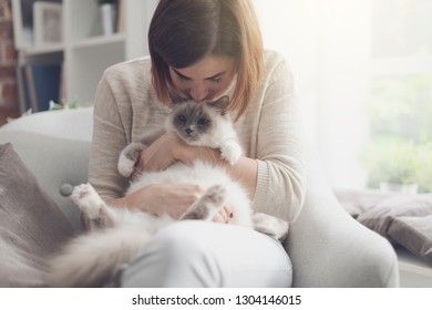 Young happy woman sitting on the armchair in the living room and petting her beautiful cat