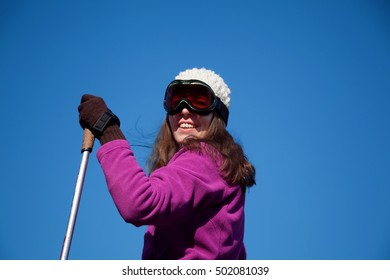 young happy woman with ski sticks doing winter sports