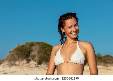 Young happy woman smiling into the camera at the beach