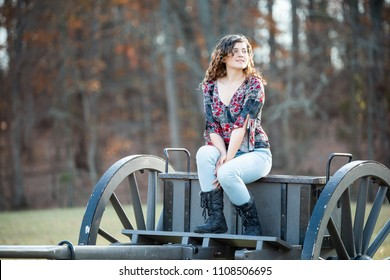 Young happy woman smiling sitting on old cannon carriage in Manassas National Battlefield Park in Virginia where Bull Run battle was fought, sunlight
