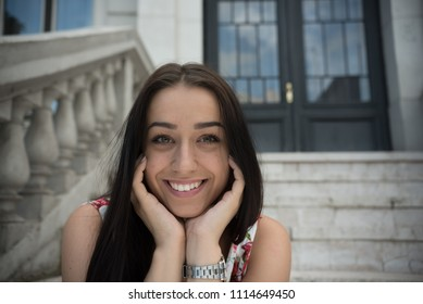 young happy woman smiling while sitting on steps out side of building