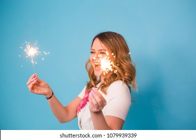Young happy woman with sparklers celebrate and laugh on blue background