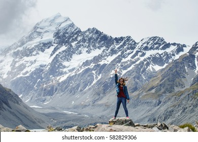 Young happy woman standing and raised hands on the Edge of Hooker Glacier Lake with Aoraki Mt. Cook in the Background