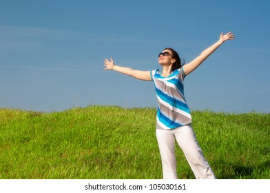 Young happy woman standing  in summer meadow  expressing freedom
