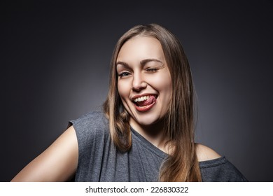 Young Happy Woman Sticking Out Her Tongue Over a Grey Background