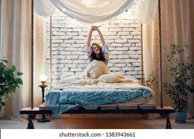 Young happy woman stretching in bed after wake up in her modern apartment. Good morning, carefree concept