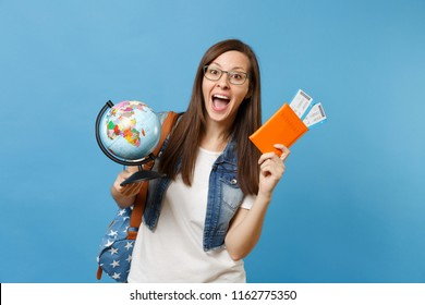 Young happy woman student in glasses with backpack holding world glove, passport, boarding pass tickets isolated on blue background. Education in university college abroad. Air travel flight concept