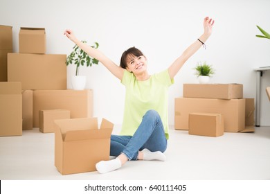 Young happy woman, a student, moved into a new apartment. Unpacks boxes in the new house. She raised her hands up as a sign of success.