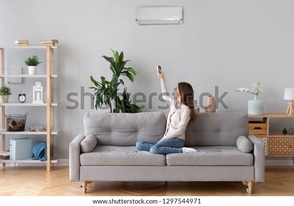 快適な家庭のソファに座るエアコンをつけ、居間のソファでくつろぐレディー、リビングルームのリモコンを持つリビングルームのレディー、より涼しいシステムで快適な温度を設定する