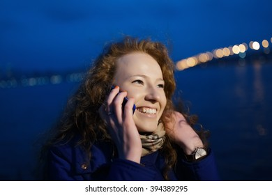 Young happy woman talking by phone in evening city at river quay
