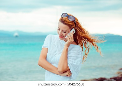 young happy woman talking on mobile phone on a beach with ocean sea background, Sardinia Italy