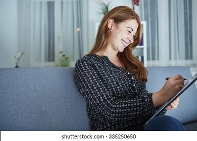 young happy woman think about christmas with list on sofa in front of christmas tree.