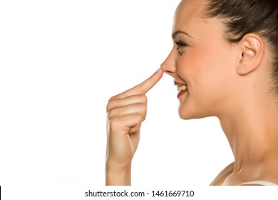 young happy woman touches her nose with her finger on a white background