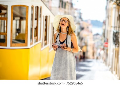 Young and happy woman tourist standing near the famous retro yellow tram on the street in Lisbon city, Portugal