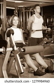 Young happy woman training quadriceps muscles using leg extension machinery in gym