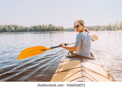 Young happy woman travels on the river. View from the back. The face is turned towards the camera. The traveler smiles.