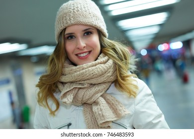 Young happy woman in underground passage during winter time.