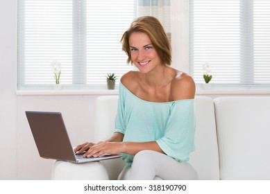 Young Happy Woman Using Laptop On Sofa