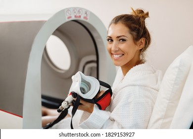 Young happy woman using oxygen mask during hyperbaric oxygen therapy at health spa.