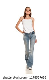 Young happy woman walking in bell bottom jeans on white background