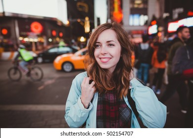 Young happy woman walking on Times Square at night, Manhattan. Inspiring New York atmosphere and a beautiful smiling girl with taxis on the background.