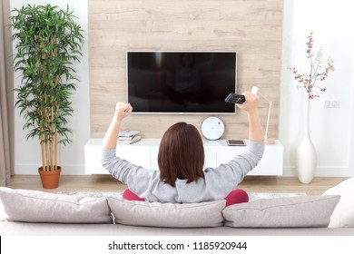 young happy woman watching excited television football sport match or TV contest