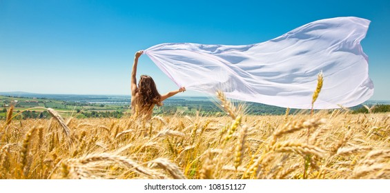 Young happy woman in wheat field with fabric. Summer set