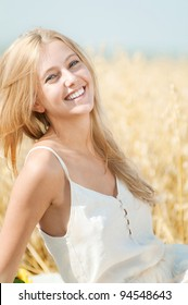 Young happy woman in wheat field. Summer picnic