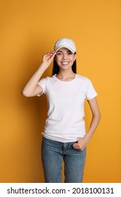 Young happy woman in white cap and tshirt on yellow background. Mockup for design