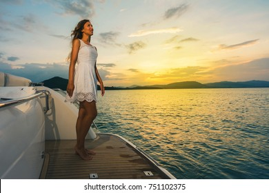 Young happy woman in white dress standing on the luxury yacht and enjoing beautiful sunset. Luxury vacation concept.