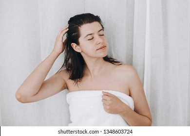 Young happy woman in white towel applying conditioner mask on hair in bathroom. Hair and body care. Slim sexy woman with natural skin enjoying spa and wellness, relaxing. Copy space