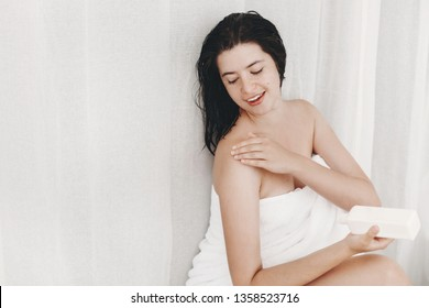 Young happy woman in white towel applying moisturizing cream on shoulder in bathroom. Skin and body care. Hand holding plastic bottle with lotion. Sexy woman relaxing, spa and wellness