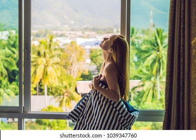 young happy woman woke up in the morning in the bedroom by the window with beautiful mountain views