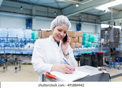Young happy woman worker in factory checking robotic line for water bottling and packing. Inspection quality control and talking on her cell phone. People at work.
