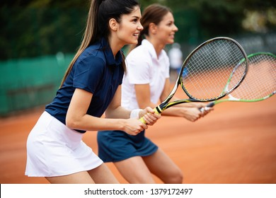 Young happy women friends playing tennis at tennis court
