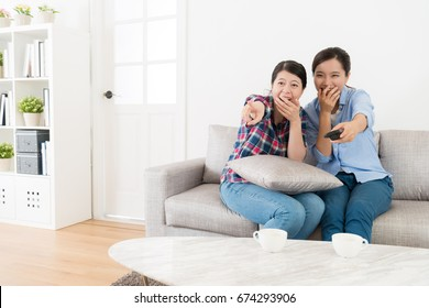 young happy women friends sitting on living room sofa at home watching tv together and looking at comedy program laughing.