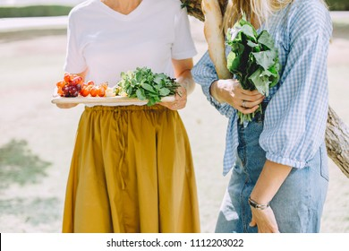 Young happy women with healthy food for summer picnic outdoor