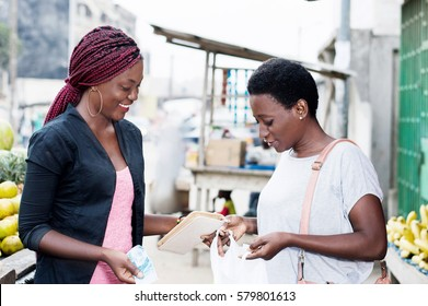 Young happy women at the market looking in a bag containing fruit.