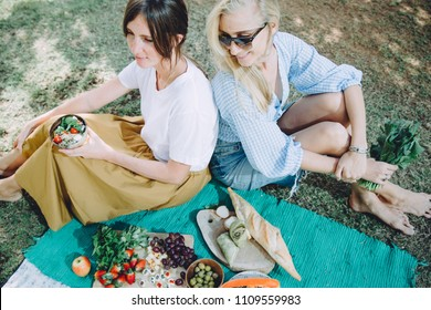 Young happy women relaxing at summer picnic with healthy food