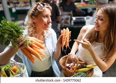 Young happy women shopping vegetables and fruits on the market