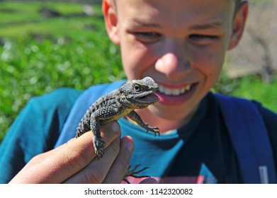 Young happy zoologist holding lizard in hands outdoors