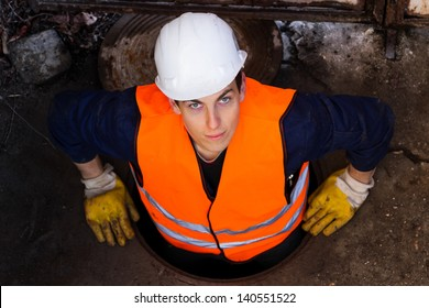 Young hard worker in his protective clothing going out from the sewage and looking directly at the camera.  Serbia.