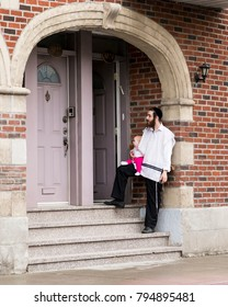 Young Hasidic Orthodox Jew father standing on stairs holding cute red-haired baby on his knee, Van Horne Street, Outremont sector, Montreal, Quebec, Canada, June 12, 2015