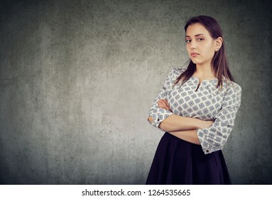 Young haughty woman looking overconfident while standing with arms crossed on gray background