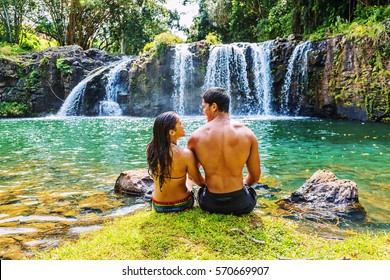 Young Hawaiian couple enjoying a moment together after a swim in a pool under a beautiful hidden waterfall